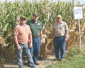 Roy Hardy, Duane Jonas and John Augustine show off some well-developed ears of corn at Augustine's farm on Kussmaul Corn Plot Day, Sept. 23, 2014